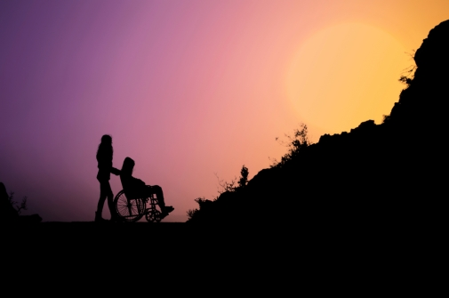 Individual pushing another person in a wheelchair with sunset.